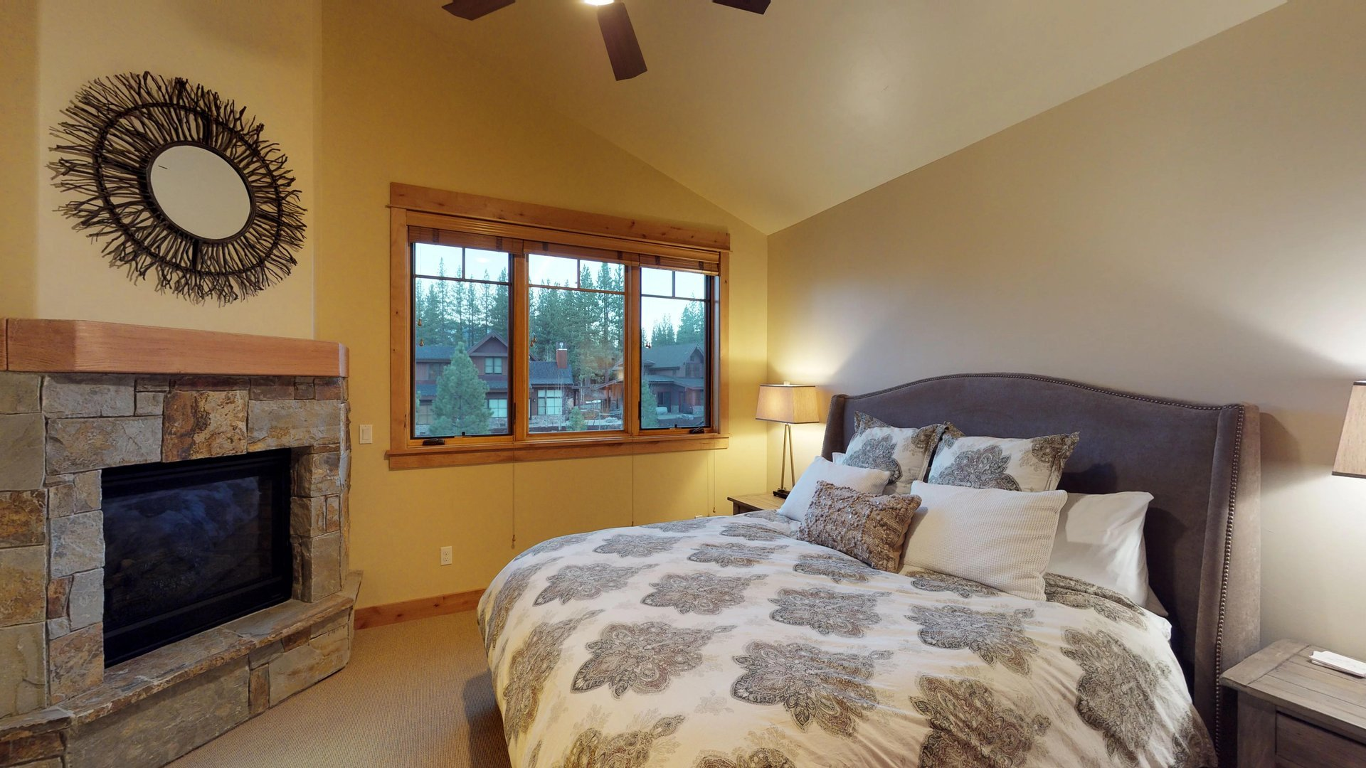 Large Bedroom Includes Two Side Tables, Fireplace, and Art on Wall.