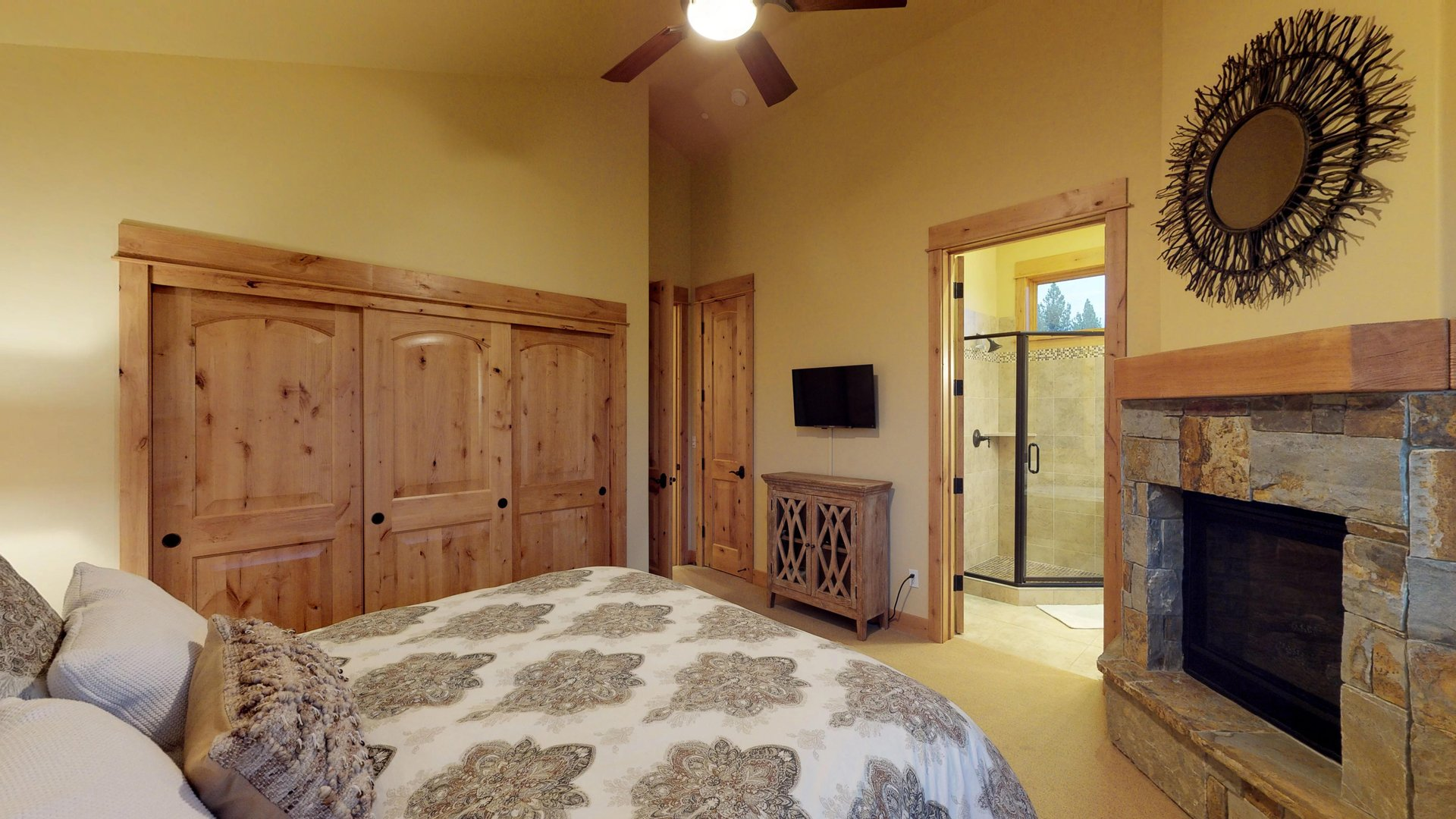 Bedroom Includes a Stone Fireplace and TV.