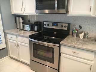 It features tile flooring, quartz counters and stainless steel appliances.
