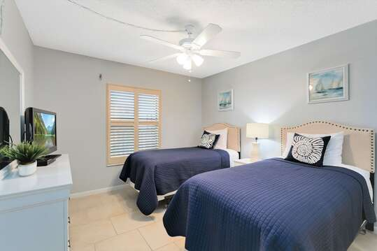 Beachy Guest bedroom with 2 twin beds, TV & closet