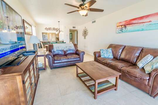 The bright living room with direct ocean views and a 65 inch TV.
