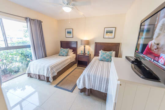 Cozy guest bedroom with two twin beds, TV and closet.