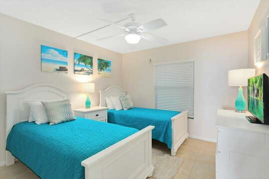 Comfortable guest bedroom with two twin beds, TV & closet