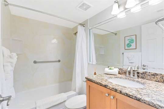 Guest bathroom with granite counters and tub/shower