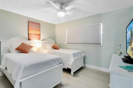 Second guest bedroom with two guest beds and a big screen TV.