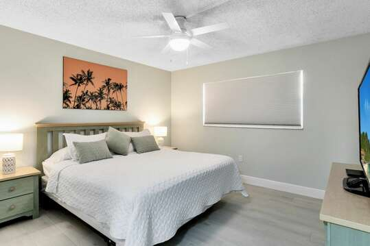 Guest bedroom with a king bed and big screen TV.