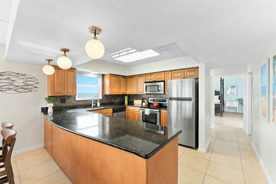 Beautiful open concept kitchen with granite counters and a view of the ocean while cooking!