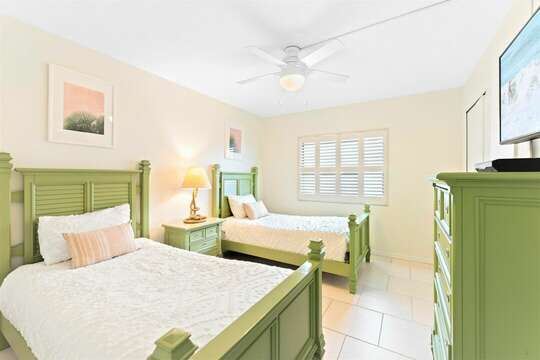 Coastal guest bedroom with two twin beds, TV & closet