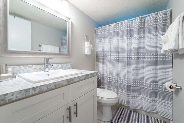 Shared family bath with tub/shower combo and single sink vanity
