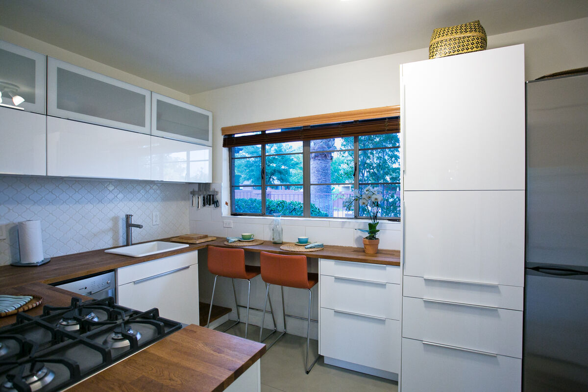The kitchen is modern and clean with a breakfast bar for two