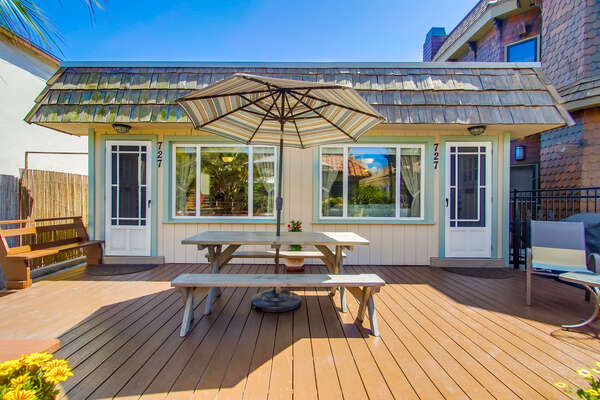 Outdoor Patio with Picnic Table and Table Umbrella.