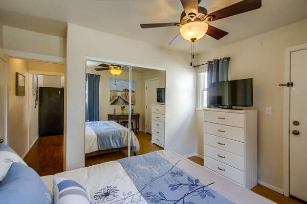 Bedroom with Large Bed, Ceiling Fan, Closet, Dresser, and TV.