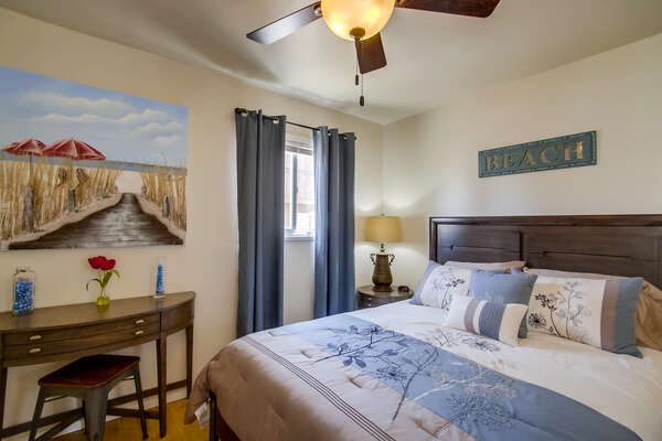 Bedroom with Large Bed, Console Table, Bench, and Ceiling Fan.