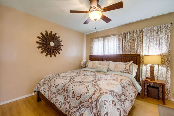 Bedroom with Large Bed, Nightstand, and Ceiling Fan.