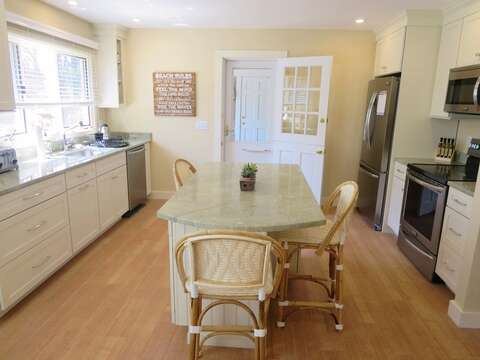 Brightly lit kitchen with center island with seating for 3. stove , refrigerator and dishwasher. 80 Landing Lane Chatham Cape Cod - New England Vacation Rentals