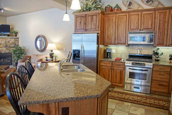 The Kitchen features granite slab counters, slate tile, and beautiful cabinetry