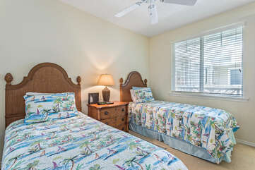 Two Twin Beds with Wooden Headboards and Large Window