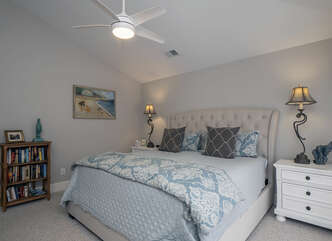 The master bedroom is located off of the great room and has a king size bed.
