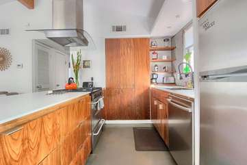 Gourmet open kitchen w/ custom cabinetry and high end stainless appliances.