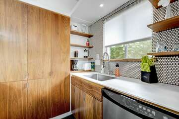 The kitchen is stocked with dishes and appliances to make meals at home.