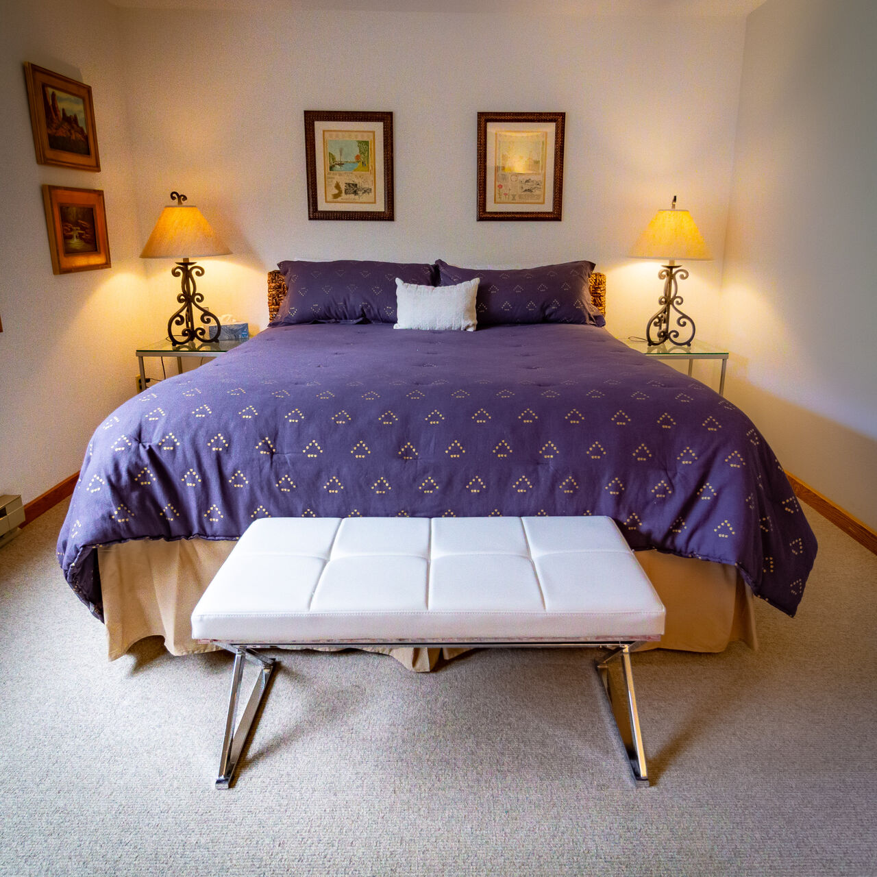 Bedroom with Purple Linens and White Bedside Bench at Colorado Vacation Cabin