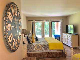 The master bedroom has a king bed, a large HDTV, sliding doors to the deck, and an en suite bathroom.