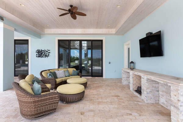 The covered lanai features a fire place, TV, and plenty of seating for all