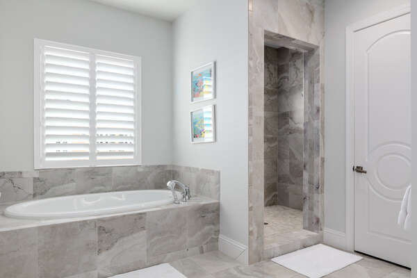 En suite bathroom features a walk-in shower, dual vanity, and garden tub