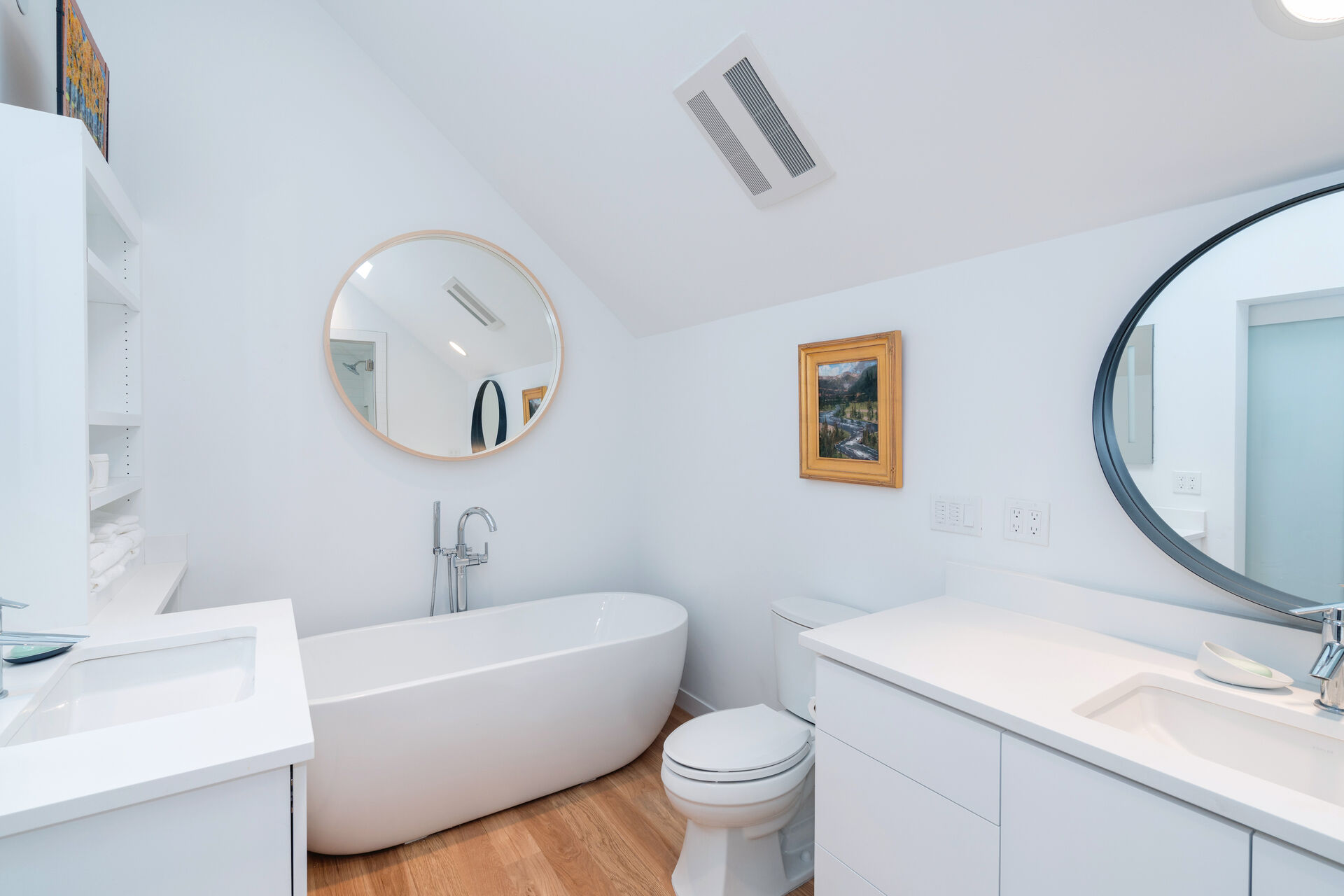 Bathroom with Soaking Tub and Vanity with Round Mirror