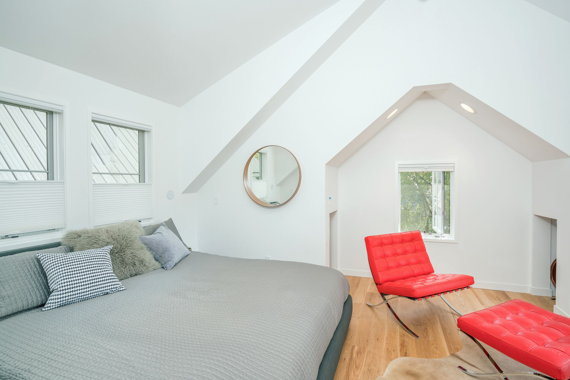 Bedroom with Comfy Grey Bed and Red Lounge Chair