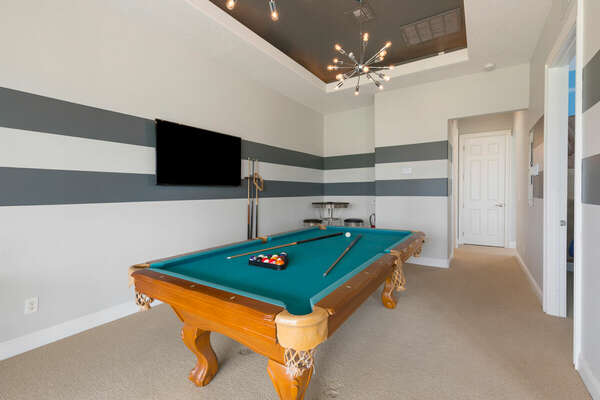 The loft area has a pool table for a friendly competition and a 50-inch TV.