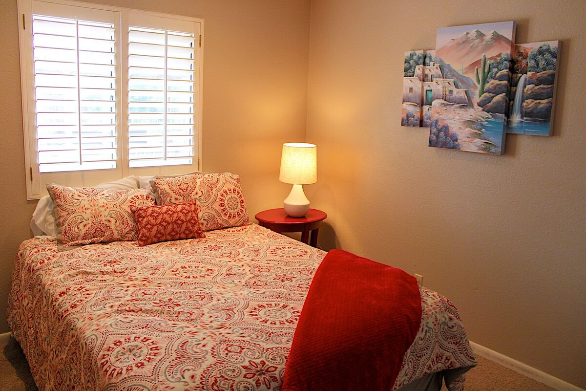A cozy second bedroom has a nice ambiance and great wall art