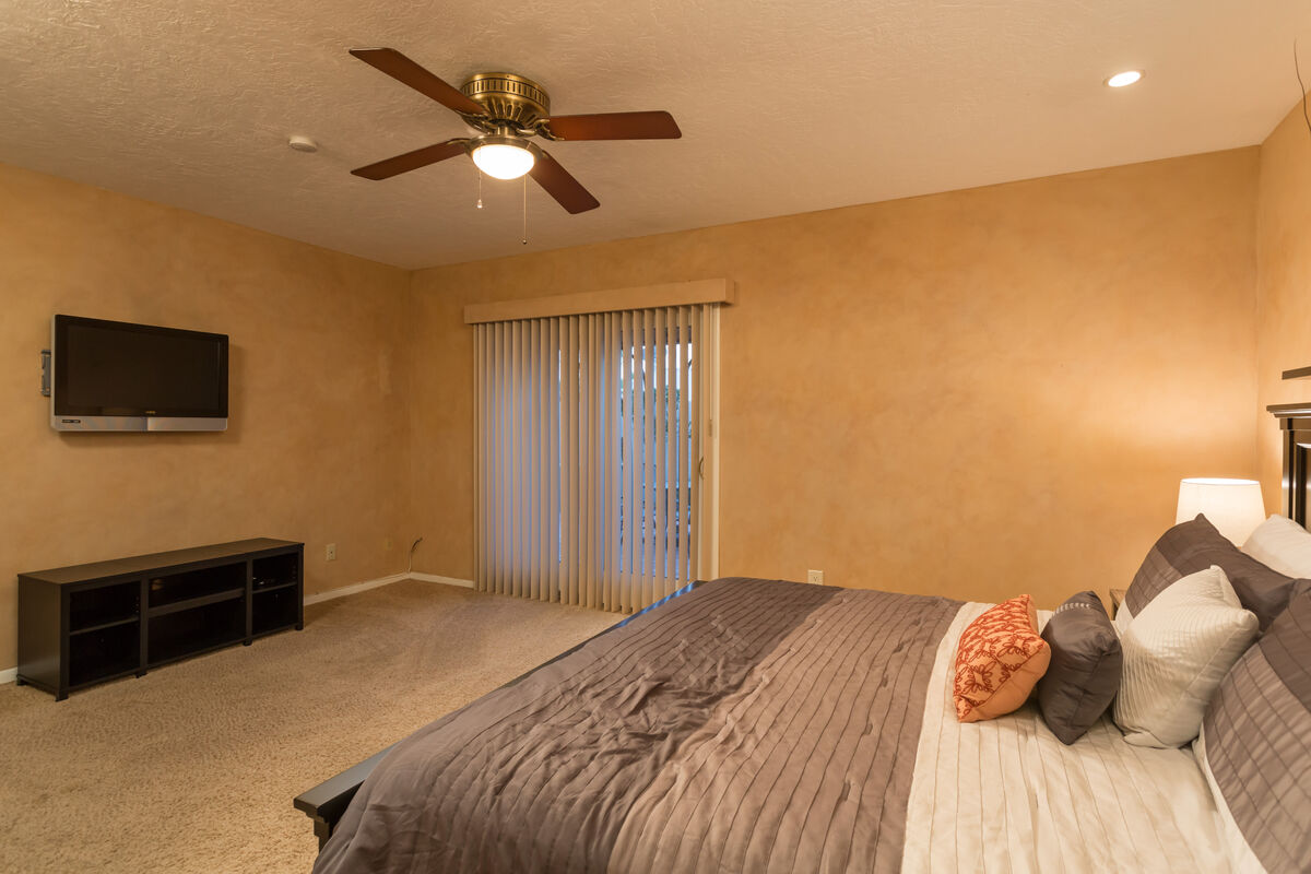 The master bedroom has a flatscreen TV and private patio to enjoy