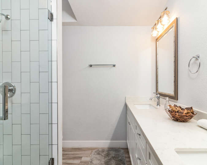 Third bathroom with walk-in shower and dual vanities.