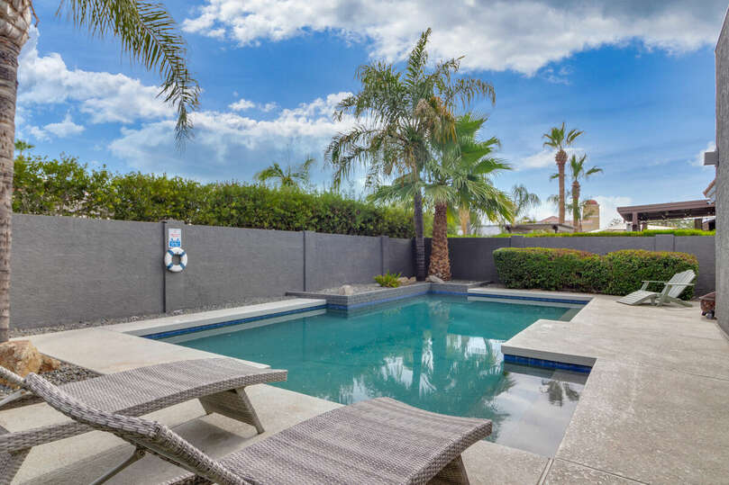 Beautiful backyard with sparkling pool, covered patio, kitchen serving window, bar seating, and a putting green.
