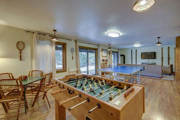 Game room on the lower level- foosball, poker table, ping pong, darts, and a TV lounge area