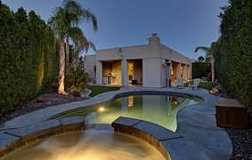 Amazing view of the pool, hot tub and the house at night