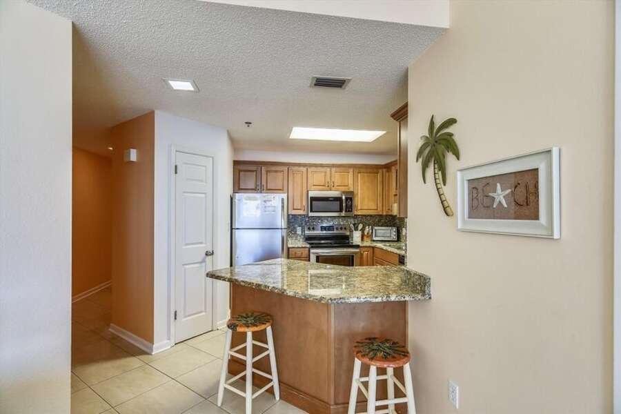 Fully Equipped Kitchen with Granite Countertops, Stainless Steel Appliances and Extra Seating at the Breakfast Bar