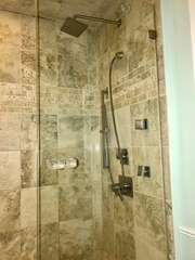 The master bathroom walk-in shower is equipped with a rain head and body sprays.