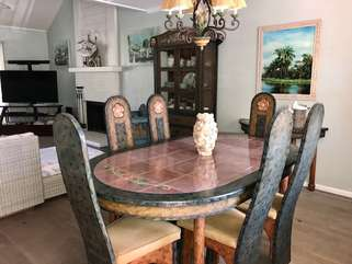 The dining table near the kitchen makes it easy to serve meals and enjoy the large TV.