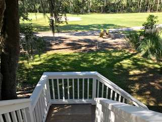 Steps lead to the small backyard with the golf course beyond.