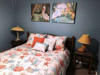 The guest bedroom has a queen size bed with  pretty coastal bedding.