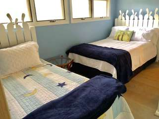 The open loft bedroom has a full size and twin size bed. A small dresser is available.