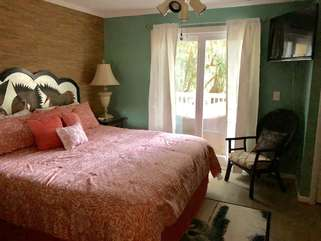 The master bedroom has an HDTV; an adjoining bathroom and sliding doors that lead to the open deck.
