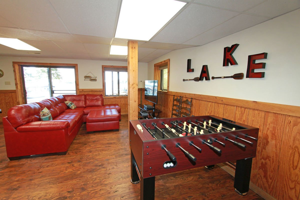 Foosball Table, Sectional Sofa, and TV.