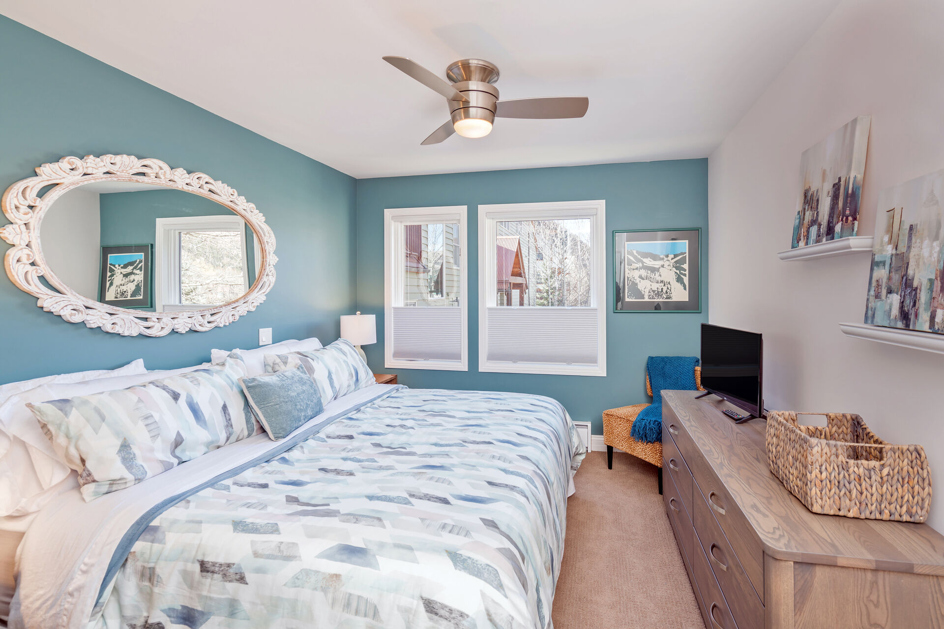Bedroom with Large Bed, Ceiling Fan, Drawer Dresser, TV, and Chair