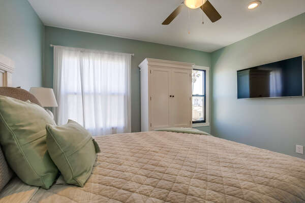 Master Bedroom Features Mounted TV on Wall.