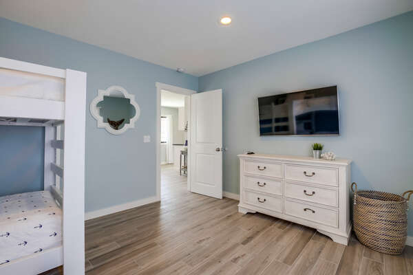 Bedroom Includes White Dresser and TV.