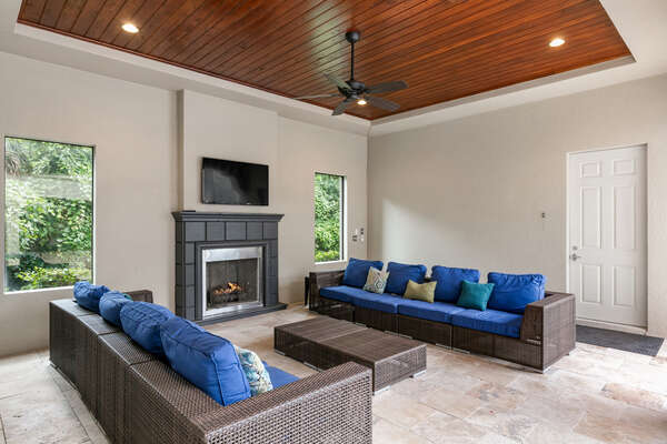 Lounge in this covered lanai with sofa seating and a SMART TV