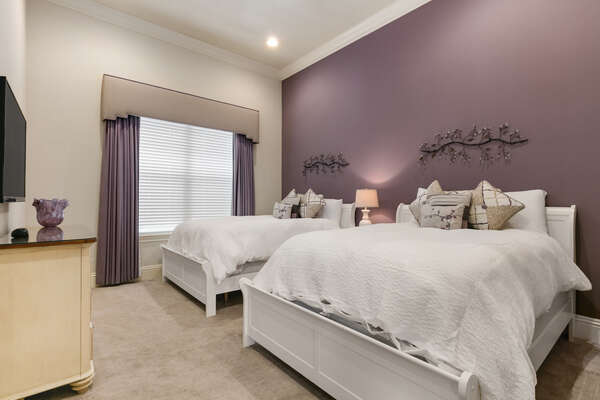 This bedroom located on the first floor features two queen beds, SMART TV, and en-suite bathroom
